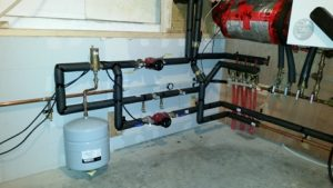 Ground loop manifold and pumps for radiant hydronic surfaces and ventilation cooling coil.